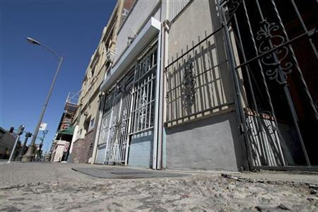 Crumbling sidewalks and shuttered businesses line a downtown street in Stockton, California, June 27, 2012. REUTERS/Kevin Bartram