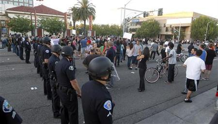 Police officers from Orange County in riot gear walk towards protesters attempting to occupy the corner of Anaheim Blvd. and Broadway to demonstrate against recent police shootings in Anaheim, California July 24, 2012. REUTERS/Alex Gallardo