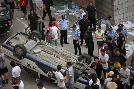 Police officers stands next to a damaged police car after demonstrators occupied the local government building during a protest against an industrial waste pipeline under construction in Qidong, Jiangsu Province July 28, 2012. REUTERS-Carlos Barria