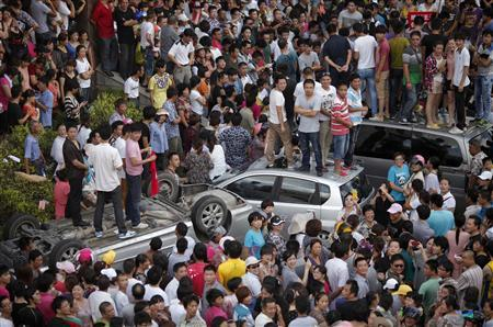 Local residents stand on smashed cars as they occupy the local government building during a protest against an industrial waste pipeline under construction in Qidong, Jiangsu Province July 28, 2012. REUTERS-Carlos Barria