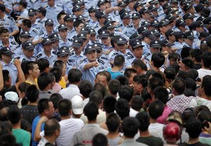 Police officers try to calm the crowd during a protest against an industrial waste pipeline under construction in Qidong, Jiangsu Province July 28, 2012. REUTERS-Carlos Barria