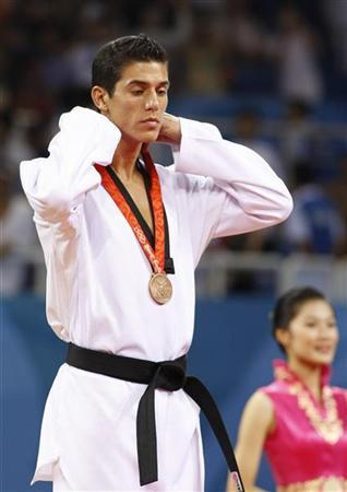 Bronze medallist Steven Lopez of the U.S. adjusts his medal strap during the medal ceremony for the men's -80kg taekwondo competition at the Beijing 2008 Olympic Games, August 22, 2008. REUTERS/Alessandro Bianchi