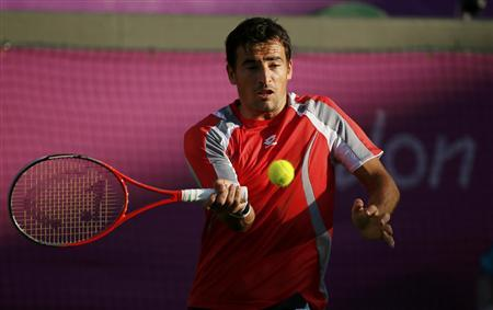 Croatia's Ivan Dodig returns to Argentina's Juan Martin del Potro in their men's singles tennis match at the All England Lawn Tennis Club during the London 2012 Olympic Games July 28, 2012. REUTERS/Lucy Nicholson