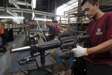A former illegal gunsmith inspects a newly assembled multi-action shotgun at Shooters Arms, a gun manufacturing company exporting different kinds of weapons to other countries, in Cebu city in central Philippines July 7, 2012. REUTERS/Erik De Castro
