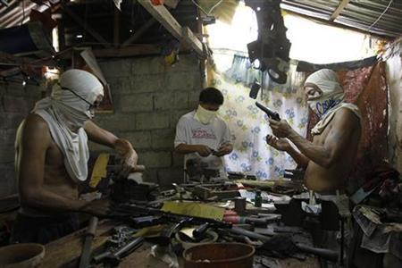 Filipino gunsmiths work in an illegal makeshift gun factory on the outskirts of Danao in central Philippines July 8, 2012. REUTERS/Erik De Castro