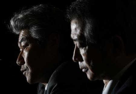 Nomura Holdings Inc outgoing Chief Executive Kenichi Watanabe (R) sits beside incoming Chief Executive Koji Nagai at a news conference in Tokyo July 26, 2012. REUTERS/Yuriko Nakao