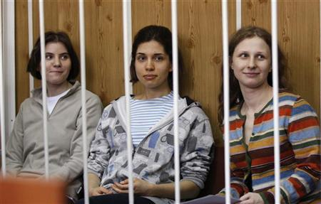 Members of female punk band ''Pussy Riot'', Nadezhda Tolokonnikova (C), Maria Alyokhina (R) and Yekaterina Samutsevich, sit behind bars before a court hearing in Moscow, July 20, 2012. Three members of ''Pussy Riot'' were detained on February 21 after they stormed into Moscow's main cathedral to sing a protest song against Vladimir Putin and criticised the Russian Orthodox Church's support for Putin REUTERS/Tatyana Makeyeva