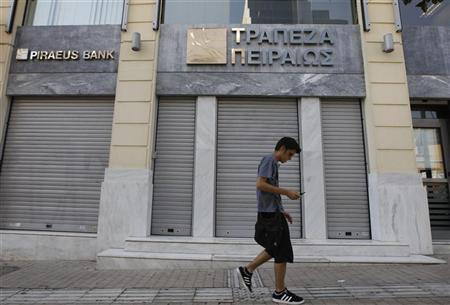 A man walks outside of a closed Piraeus bank branch in central Athens July 16, 2012. REUTERS/John Kolesidis