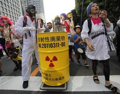 An anti-nuclear protester wearing a gas mask beats a mock nuclear waste container during a demonstration near Tokyo Electric Power Co. headquarters building in Tokyo July 29, 2012. About 10,000 people took part in the protest, according to local media. REUTERS/Yuriko Nakao