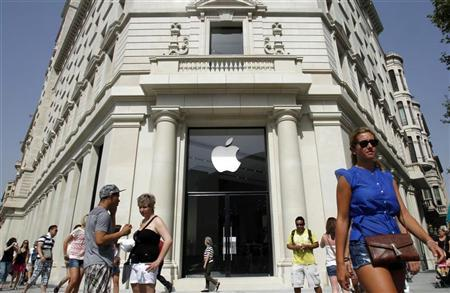 People walk past a closed shop, which will be opened and inaugurated as the largest Apple store in southern Europe on July 28, at Passeig de Gracia, in Barcelona July 26, 2012. The iPhone revolutionized the smartphone industry, driving Apple's expansion into Europe and China and, after just half a decade, yields about half its annual $100 billion revenue haul. REUTERS/Albert Gea
