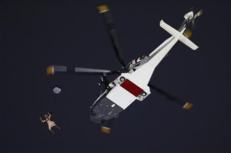Actors portraying the Queen and James Bond arrive via parachute after jumping from a helicopter during the opening ceremony of the London 2012 Olympic Games at the Olympic Stadium July 27, 2012. REUTERS/Murad Sezer