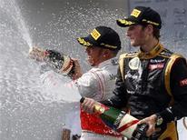 Piloto da McLaren Lewis Hamilton (E) e da Lotus Romain Grosjean comemoram com champagne após conquistarem o pódio no Grande Prêmio da Hungria. 29/07/2012 REUTERS/Bernadett Szabo