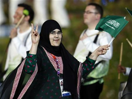 Saudi Arabia's Wojdan Ali Seraj Abdulrahim Shaherkani gestures as she walks with the contingent in the atheletes parade during the opening ceremony of the London 2012 Olympic Games at the Olympic Stadium July 27, 2012. Saudi Arabia's first female Olympic athletes made their appearance at the opening ceremony to the London Games on Friday, dressed in traditional hijabs, or Islamic headscarfs. On Thursday, International Judo Federation president Marius Vizer said Shaherkani would have to fight without a hijab - a decision that is likely to cause controversy in Saudi Arabia, where female participation in sports has long been a controversial issue. REUTERS/Suzanne Plunkett