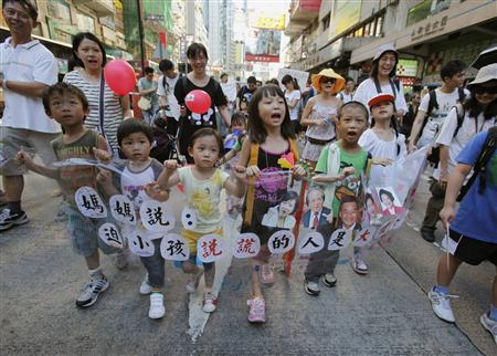 Children chant slogans as they carry a banner featuring portraits of government officials, including Hong Kong's Chief Executive Leung Chun-ying (3rd L), during a protest march against a Chinese patriotic education course in Hong Kong July 29, 2012. Thousands of people including parents, teachers and children took to the streets on Sunday against the course, which is set to begin in the territory in September, saying it is aimed at brainwashing students. The Chinese characters on the banner read: ''Mum said, those who force kids to lie are bad guys''. REUTERS/Bobby Yip