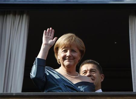 German Chancellor Angela Merkel waves as she stands next to her husband Joachim Sauer (R) on arrival for the opening of the Bayreuth Wagner opera festival at the Gruener Huegel (Green Hill) opera house in Bayreuth July 25, 2012. REUTERS/Michaela Rehle