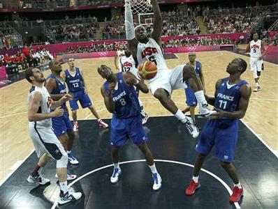 Lebron James of the U.S. hangs on the rim as France's Ali Traore (L) and Florent Pietrus (R) look on during their men's Group A basketball match at the London 2012 Olympic Games in the Basketball arena July 29, 2012. REUTERS/Sergio Perez