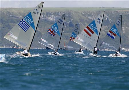 A fleet of Finn class dinghies sail during the first race at the London 2012 Olympic Games in Weymouth and Portland, southern England, July 29, 2012. REUTERS/Pascal Lauener
