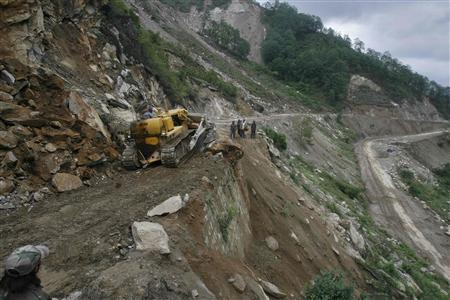 A bulldozer clears a landslide from India's Tezpur-Tawang highway, which runs to the Chinese border, in the northeastern Indian state of Arunachal Pradesh May 31, 2012. REUTERS/Frank Jack Daniel