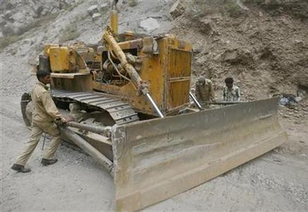 Labourers employed by the Indian army, adjust a bulldozer blade on India's Tezpur-Tawang highway which runs to the Chinese border in Arunachal Pradesh May 28, 2012. Picture taken May 28, 2012. REUTERS/Frank Jack Daniel