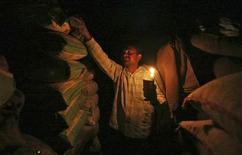 Рабочий при свете свечи проверяет мешки с рисом на оставшемся без света оптовом рынке в Джамму (Индия), 16 января 2012 года. Сбой электроснабжения оставил в понедельник без электричества более 300 миллионов человек в Дели и северной части Индии, став худшей аварией подобного рода в стране за примерно 10 лет. REUTERS/Mukesh Gupta
