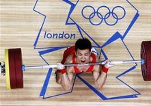 Китайский тяжелоатлет У Цзинбяо поднимает штангу весом 56кг на Олимпиаде-2012 в Лондоне, 29 июля 2012 года. В понедельник на летних Играх в Лондоне будут разыграны 12 комплектов медалей, включая награды в тяжелой атлетике. REUTERS/Dominic Ebenbichler