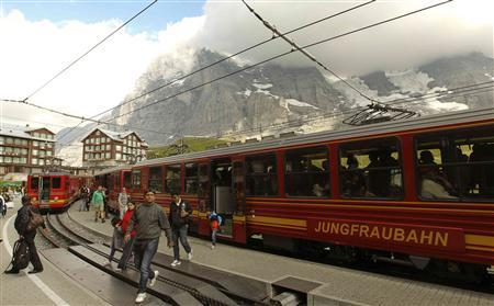Tourists leave a train of the Jungfraubahn railways at the Kleine Scheidegg station (altitude 2061 metres/6762 feet) near the Swiss mountain resort of Grindelwald July 25, 2012. REUTERS/Arnd Wiegmann