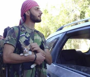 A member of the Free Syrian Army holds a cat at Anadan in Aleppo July 29, 2012. Picture taken July 29, 2012. REUTERS/Shaam News Network/Handout
