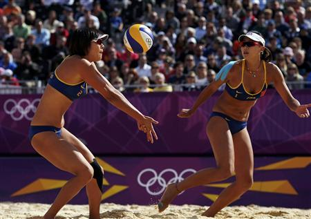 China's Zhang Xi (L) returns a shot as her teammate Xue Chen watches during their women's preliminary round beach volleyball match against Switzerland at the London 2012 Olympic Games at Horse Guards Parade July 30, 2012. REUTERS/Marcelo del Pozo