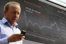 A man passes a screen showing the activity of the FTSE index at Canary Wharf financial district in London August 5, 2011. REUTERS/Luke MacGregor