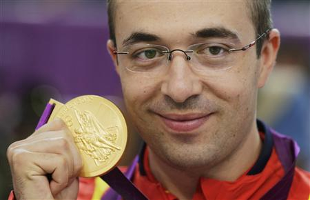 Romania's Alin George Moldoveanu poses with his gold medal during the 10m air rifle men's victory ceremony at the Royal Artillery Barracks during the London 2012 Olympic Games July 30, 2012. REUTERS/Cathal McNaughton
