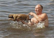 Мужчина держит собаку во время купания в Волге в Конаково 18 июля 2010 года. Рабочая неделя в столице вновь будет жаркой, ожидают синоптики. REUTERS/Denis Sinyakov