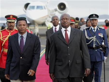 Uganda's President Yoweri Museveni (R) is escorted by Tanzanian Foreign Affairs minister Bernard Membe (L) upon arrival at Kilimanjaro Airport in Tanzania, May 21, 2008. REUTERS/Antony Njuguna