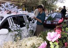 An Afghan worker decorates a wedding car with artificial flowers in Kabul on July 5, 2002. REUTERS/Beawiharta
