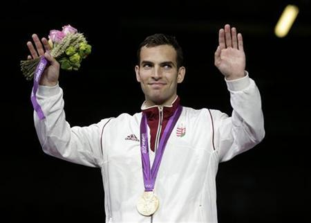 Gold medallist Aron Szilagyi of Hungary celebrates on podium during the award ceremony for men's sabre individual fencing competition at the ExCel venue at the London 2012 Olympic Games July 29, 2012. REUTERS/Max Rossi