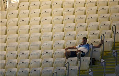 A spectator sits among empty seats as he waits for the start of the final session on the first day of the swimming competition at the London 2012 Olympic Games at the Aquatics Centre July 28, 2012. REUTERS/Jorge Silva