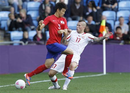 South Korea's Yun Suk-young (L) fights for the ball with Switzerland's Michel Morganella during their men's Group B football match in the London 2012 Olympic Games at the City of Coventry stadium July 29, 2012. REUTERS/Alessandro Garofalo