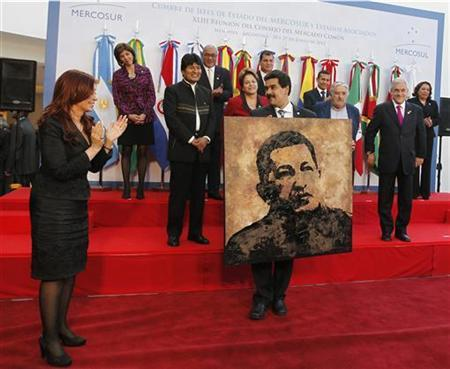 Argentina's President Cristina Fernandez de Kirchner (front L) applauds after giving Venezuela's Foreign Minister Nicolas Maduro a portrait of President Hugo Chavez painted by Argentine artist Norberto Filippo as a souvenir during the annual summit of the Mercosur trade bloc in Mendoza, June 29, 2012. REUTERS/Enrique Marcarian
