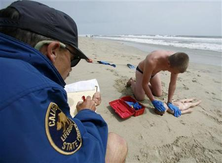California lifeguard trainee Robert Phelps it tested by instructor Ed Vodrazka (L) as he rescues a child prop from the ocean and performs CPR in Huntington Beach, California June 2, 2007. REUTERS/Mike Blake