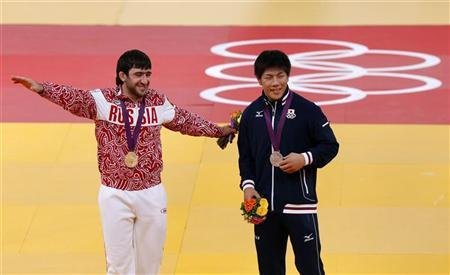 Gold medallist Mansur Isaev of Russia (L) and silver medallist Riki Nakaya of Japan smile on the podium after the men's -73kg final judo match at the London 2012 Olympic Games July 30, 2012. REUTERS/Kim Kyung-Hoon