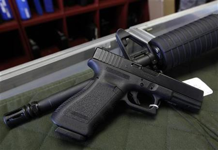 A Glock 22 pistol is seen laying on a Palmetto M4 assault rifle at the Rocky Mountain Guns and Ammo store in Parker, Colorado July 24, 2012. REUTERS/Shannon Stapleton