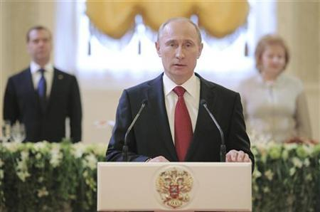 Russia's new President Vladimir Putin (front) speaks during a reception, dedicated to the start of his term as Russia's new President, with his wife Lyudmila (R) and former President Dmitry Medvedev seen in the background, at the Kremlin in Moscow, May 7, 2012. REUTERS/Alexsey Druginyn/RIA Novosti/Pool