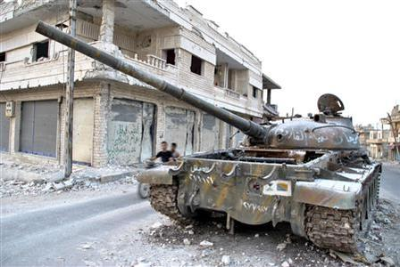 A destroyed tank of Syrian President Bashar al Assad's forces is seen after clashes with the Free Syrian Army in the Rasten area, near Homs July 29, 2012. REUTERS/Fadi Zaidan