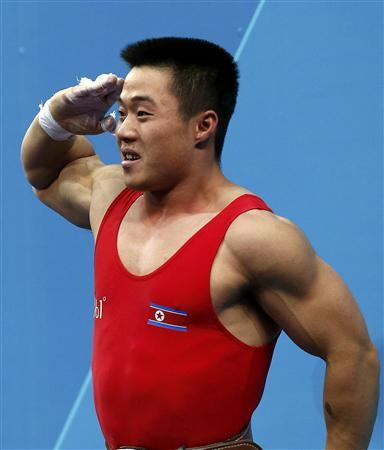 North Korea's Un Guk Kim salutes celebrating his new world record in total of the men's 62Kg weightlifting competition at the London 2012 Olympic Games July 30, 2012. REUTERS/Dominic Ebenbichler