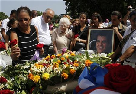 Ofelia Acevedo, wife of Oswaldo Paya, (L), one of Cuba's best-known dissidents, places a rose on the tomb of her husband during his burial in Havana July 24, 2012. REUTERS/Stringer