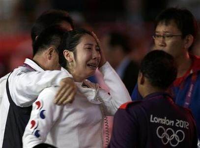 South Korea's Shin A Lam (C) reacts as she is escorted after being defeated by Germany's Britta Heidemann (not seen) during their women's epee individual semifinal fencing competition at the ExCel venue at the London 2012 Olympic Games July 30, 2012. REUTERS/Max Rossi