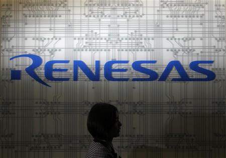 A receptionist passes by the logo of Renesas Electronics Corp at the company's headquarters in Tokyo July 3, 2012. REUTERS/Yuriko Nakao