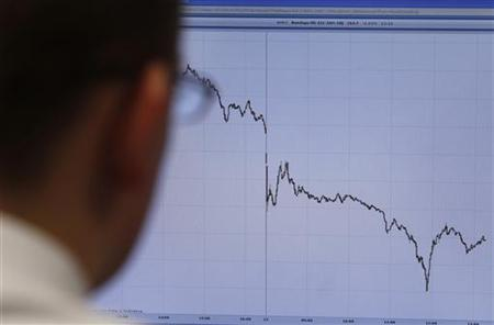 A trader poses in front of a screen on a trading floor in London January 22, 2010. REUTERS/Stefan Wermuth