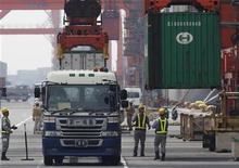 Рабочие следят за погрузкой контейнера на грузовик в порту в Токио, 25 июля 2012 года. Крупные азиатские экспортеры - Япония, Южная Корея и Тайвань - демонстрируют все более убедительные признаки экономического стресса, так как долговой кризис еврозоны, замедление в Китае и слабая активность в США влияют на мировой спрос. REUTERS/Yuriko Nakao