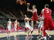 Российский баскетболист Андрей Кириленко (в центре) бросает мяч в кольцо команды Китая на групповом этапе Олимпиады в Лондоне, 31 июля 2012 года. Сборная России по баскетболу уверенно обыграла команду Китая на групповом этапе Олимпиады в Лондоне. REUTERS/Mike Segar
