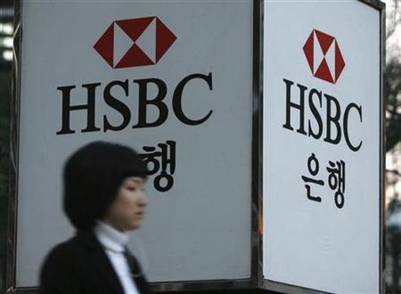 A woman walks past a HSBC logo at a branch office in Seoul March 5, 2008. REUTERS/Jo Yong-Hak
